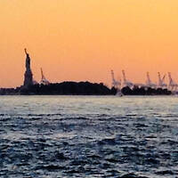 The Statue of Liberty at sunset flanked by construction cranes reminds us that the monument is a symbol of our historical role as refuge for immigrants and chief exporter of freedom. w